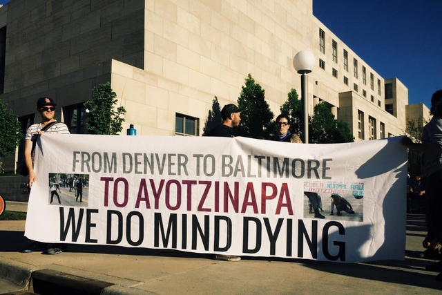 Protesters holding banner which reads 'From Denver to Baltimore to Ayotzinapa We Do Mind Dying'
