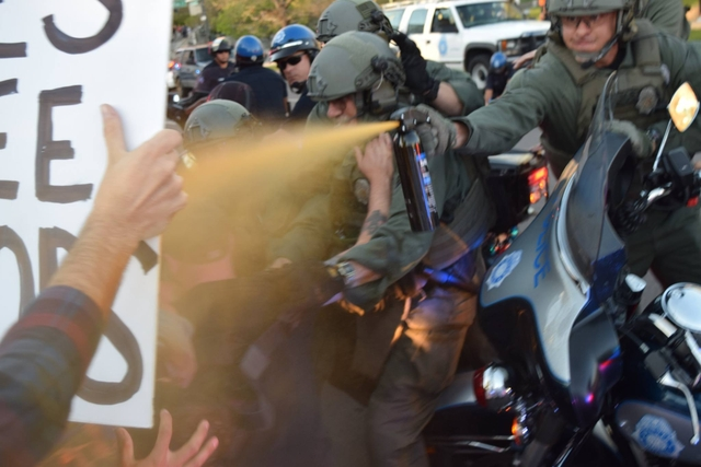 Eager cop sprays protesters from behind motorcycles