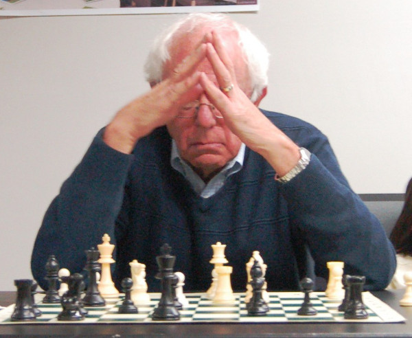 Senator Sanders sitting in front of a chess board.